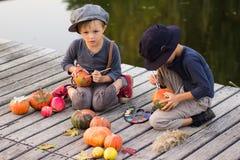 De positieve kinderen schilderen kleine Halloween-pompoenen Stock Foto