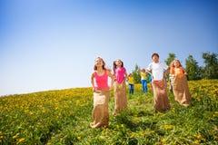 De positieve kinderen springen in zakken en het spelen Stock Foto