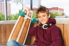 De positieve leuke jongen houdt skateboard terwijl het zitten Stock Afbeeldingen