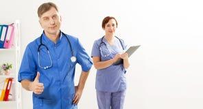 De positieve mannelijke arts toont als teken en vrouwelijke arts met omslag in medisch bureau, medische verzekering, selectieve e stock afbeeldingen