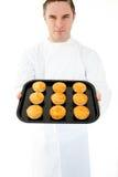 De positieve mannelijke muffin van de kokholding Stock Foto's