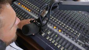 De positieve mens in hoofdtelefoons spreekt in microfoon en maakt correcte luider op materiaal in radiostudio stock footage