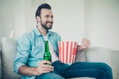 De positieve vrolijke knappe gebaarde mens met snack en refreshmen royalty-vrije stock foto's