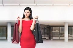 De positieve vrouw in rood dichtbij een wandelgalerij, sluit omhoog Stock Afbeelding