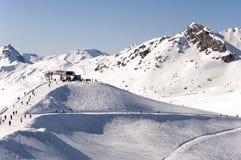 De post, de skiërs en de ski van de stoeltjeslift piste in Alpen stock afbeeldingen