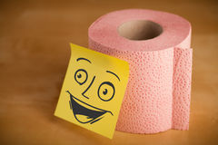 De post-itnota met smileygezicht sticked op een toiletpapier Royalty-vrije Stock Foto