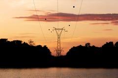 De post van de silhouethoogspanning, de toren van de machtstransmissie bij Sirindhorn-Dam in de ochtendtijd stock foto's