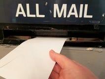 De post van een brief in de postgroef bij het postkantoor stock foto's