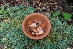 De pot van de aardewerkbloem met gebarsten binnen stukken stock afbeelding
