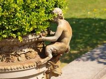 De pot van de bloem met een standbeeld van Satyr Koninklijke Serres Royalty-vrije Stock Afbeelding