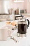 De pot van de koffie op keukenteller met sconen Stock Fotografie