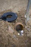 De pot van gouden muntstukken verzamelde met hulp van metaaldetector, groene grasachtergrond Royalty-vrije Stock Foto