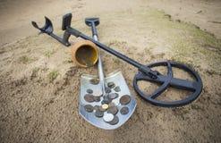 De pot van gouden muntstukken verzamelde met hulp van metaaldetector, groene grasachtergrond Stock Afbeeldingen