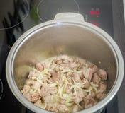De pot van het roestvrij staalijzer op een inductiekooktoestel dat het vlees met uien en wortelen voor het koken van pilau voorbe Stock Foto's