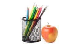 De potloden van de kleur in een zwarte houder met appel Stock Foto's