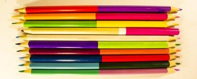 De potloden voor het trekken op papier van verschillende kleuren liggen op een wit tekeningsdocument stock afbeeldingen