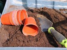 De potten en de troffel van de installatie in compost. Stock Afbeelding