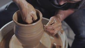 De pottenbakker creeert product op de draaibank spinnend aardewerk van de pottenbakker in langzame motie stock footage