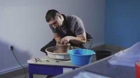 De pottenbakker creeert product op het wiel van de pottenbakker De mens creeert zacht kruik van klei stock videobeelden