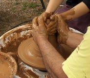De pottenbakker en het kind overhandigen vormende modder royalty-vrije stock fotografie
