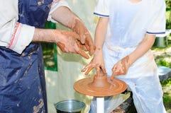 De pottenbakker onderwijst de jongen om aan pottenbakkerswiel te werken royalty-vrije stock foto