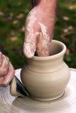 De pottenbakker overhandigt pot Stock Afbeeldingen