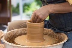 De pottenbakker past voor op een pottenbakkerswiel op Royalty-vrije Stock Foto