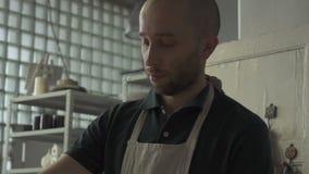 De pottenbakker verdeelt de kleimassa in gedeelten in de workshop stock video