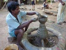 De pottenbakker werkt klei aan een wiel Stock Fotografie