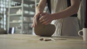 De pottenbakker in workshop kneedt een mengsel van klei om ceramische schotels te maken stock video