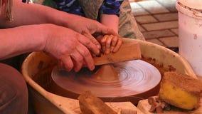 De pottenbakkers overhandigt leidend kind op het ceramische wiel stock video