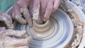 De pottenbakkers` s handen werken met klei aan een pottenbakkers` s wiel stock footage
