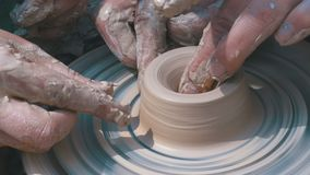 De pottenbakkers` s handen werken met klei aan een pottenbakkers` s wiel stock video