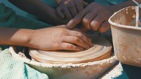 De pottenbakkers` s handen werken met klei aan een pottenbakkers` s wiel stock videobeelden