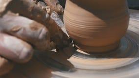 De pottenbakkers` s handen werken met klei aan een pottenbakkers` s wiel Langzame Motie stock video