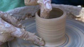 De pottenbakkers` s handen werken met klei aan een pottenbakkers` s wiel Langzame Motie stock videobeelden