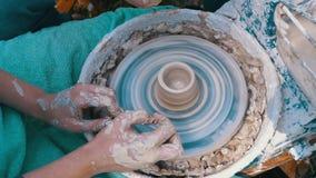 De pottenbakkers` s handen werken met klei aan een pottenbakkers` s wiel Langzame Motie stock footage