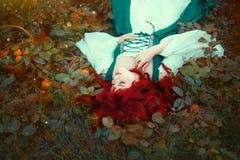 De prachtige roodharige prinses die die op de grond liggen, met bladeren wordt gescheurd, zette zacht haar hand op haar borst, ge royalty-vrije stock foto's