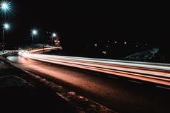 De prachtige schok het licht van auto steekt in de avond op de weg met de sterren van straatlantaarns aan royalty-vrije stock foto's