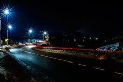 De prachtige schok het licht van auto steekt in de avond op de weg met de sterren van straatlantaarns aan royalty-vrije stock foto