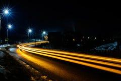 De prachtige schok het licht van auto steekt in de avond op de weg met de sterren van straatlantaarns aan royalty-vrije stock afbeelding
