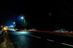 De prachtige schok het licht van auto steekt in de avond op de weg met de sterren van straatlantaarns aan stock fotografie