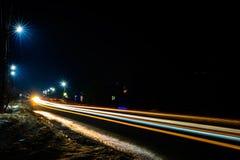 De prachtige schok het licht van auto steekt in de avond op de weg met de sterren van straatlantaarns aan stock foto's