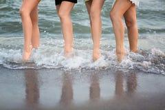 De prachtige vrouwen met lange benen lopen dichtbij het overzees op het zand De leuke benen van sportenvrouwen ` s stock fotografie