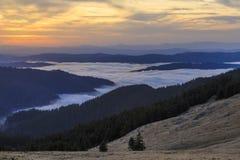 De prado de la ladera con el bosque y las nubes imagenes de archivo