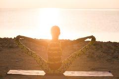 De praktijk van de yoga. De vrouw die yoga doet stelt bij zonsopgang Stock Foto's