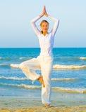 De praktijk van de yoga op een zonsopgang Stock Foto's