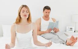 De praktijkyoga van de vrouw terwijl haar echtgenoot leest Stock Foto