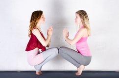 De praktijkyoga van twee aantrekkelijke sportenmeisjes in een fitness klasse Jonge vrouwen royalty-vrije stock afbeeldingen