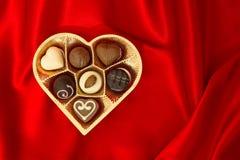De pralines van de chocolade in de gouden doos van de hartvorm Stock Fotografie